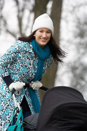 Pushing : Mother walking with baby carriage in park  portrait