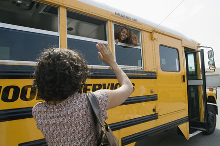 High school : Mother waving to teenage daughter on school bus