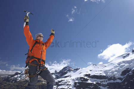 One man only : Mountain climber with arms raised on top of peak