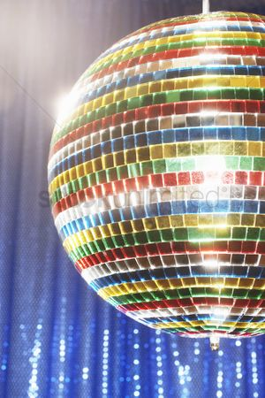 Dance : Multi-coloured disco ball in front of blue stage curtain cropped