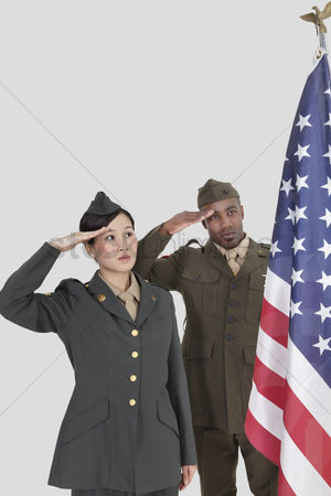 Respect : Multi-ethnic us military officers saluting american flag over gray background