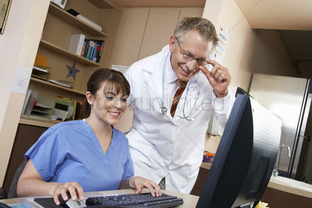 White hair : Nurse and doctor working on computer