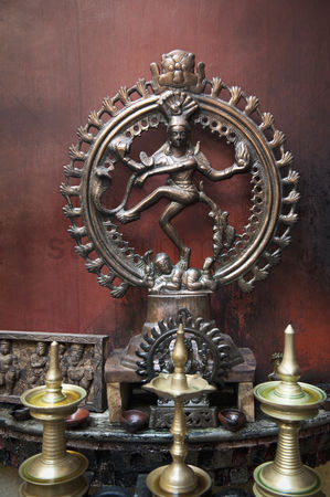 God : Oil lamps in front of a statue of nataraj  kochi  kerala  india