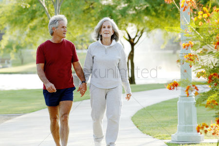 People : Old couple holding hands while walking in the park
