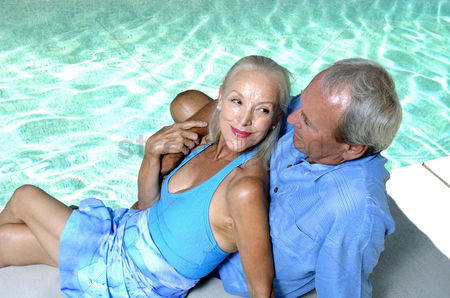 Three quarter length : Old couple relaxing by the pool side