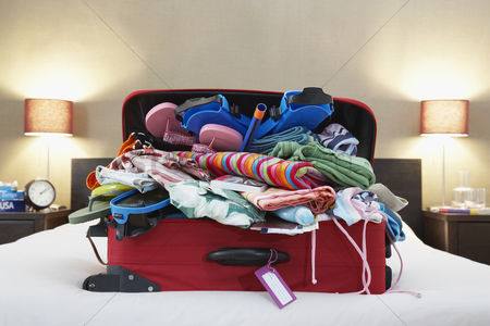 Pile : Open suitcase on bed