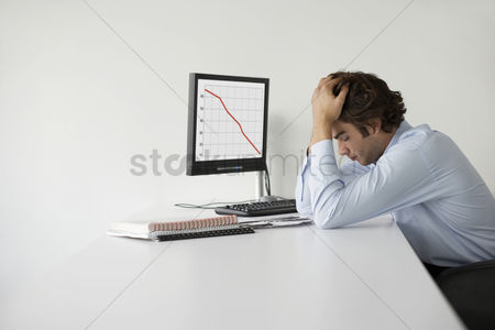 Office worker : Overworked businessman with head in hands sitting at desk in office