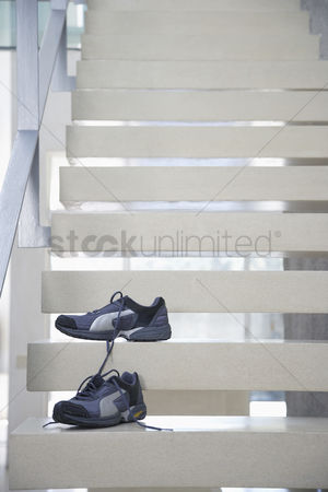 Stairs : Pair of untied athletic shoes on stairs