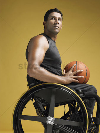 One man only : Paraplegic athlete sitting in wheelchair holding basketball side view