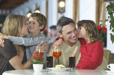 Kissing : Parents and children  7-9  with drinks embracing at restaurant