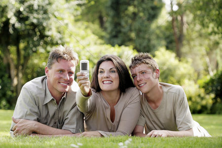 Lying forward : Parents taking picture with their son