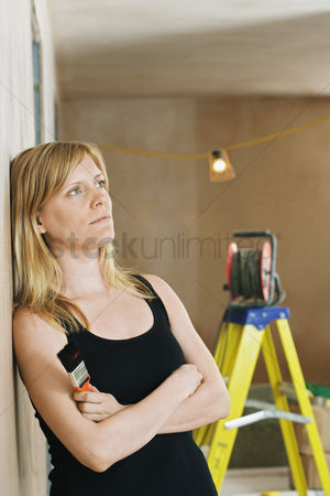 Wondering : Pensive woman leaning against wall ladder in background