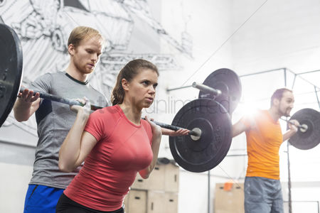 Three quarter length : People lifting barbells in crossfit gym