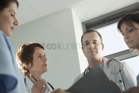 Expertise : Physicians reviewing medical chart low angle view