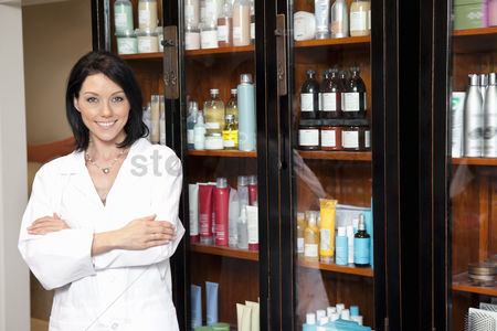 Beauty : Portrait of a beauty salon employee standing with arms crossed and cosmetics in background