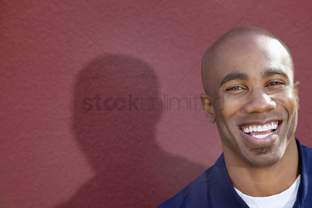 Smiling : Portrait of a cheerful african american man over colored background