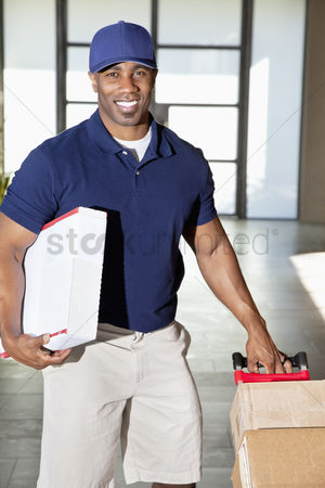 Pushing : Portrait of a happy african american man carrying delivery boxes