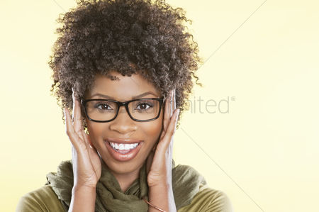 Curly hair : Portrait of a happy african american wearing glasses over colored background