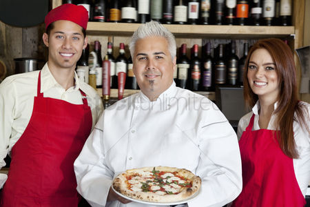 Apron : Portrait of a happy chef holding pizza with wait staff