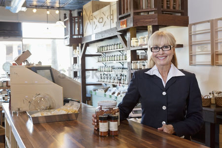 Camera : Portrait of a happy female owner standing at counter with spice jar in store