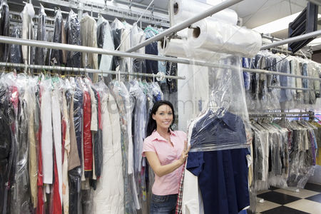 Employee : Portrait of a happy mid adult woman putting plastic to dry cleaned clothes in laundry