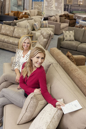 Offspring : Portrait of a happy mother and daughter in furniture store