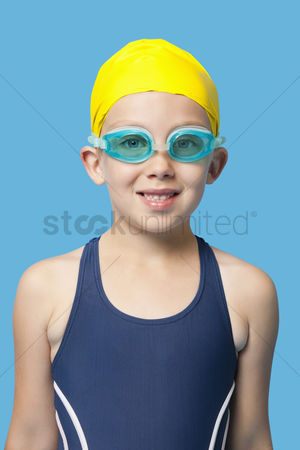 Swimmer : Portrait of a happy young girl wearing swim goggles over blue background