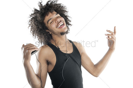 Portability : Portrait of a happy young man gesturing while listening to mp3 player over white background