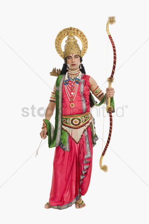 God : Portrait of a stage artist dressed-up as rama the hindu mythological character and holding a bow and arrow