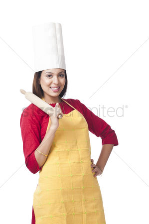 Housewife : Portrait of a woman holding a rolling pin and smiling