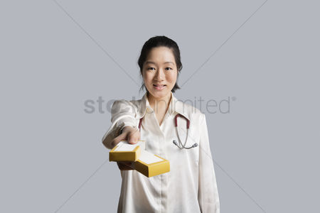 Cardboard cutout : Portrait of a young female doctor giving medicine boxes