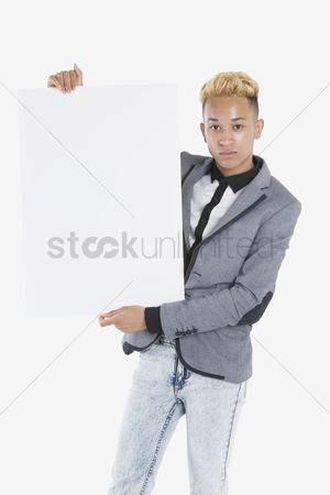 Cardboard cutout : Portrait of a young man holding blank cardboard over gray background