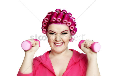 Dumbbell : Portrait of a young woman happily lifting weights