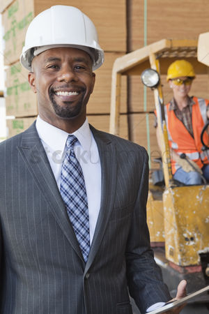 Forklift : Portrait of african american male engineer smiling with female worker in background