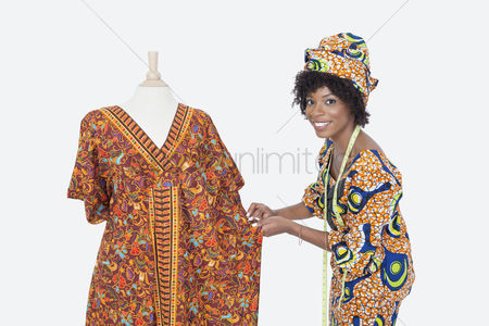 Traditional clothing : Portrait of an african american female fashion designer working on dashiki over gray background