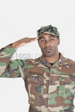 Respect : Portrait of an african american us marine corps soldier saluting over gray background