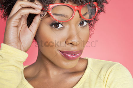 Curly hair : Portrait of an african american woman holding retro glasses over colored background