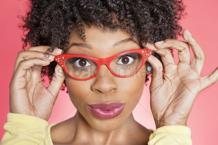 Background : Portrait of an african american woman wearing retro style glasses over colored background