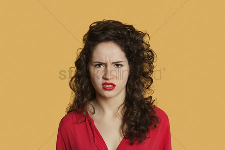 Curly hair : Portrait of angry young woman frowning over colored background