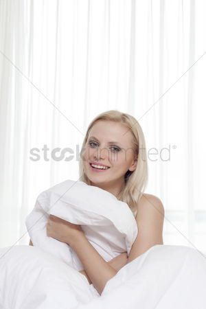 Shyness : Portrait of attractive young woman covering herself with bedsheet in bed