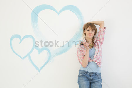 Shape : Portrait of beautiful woman holding paint brush with hearts painted on wall