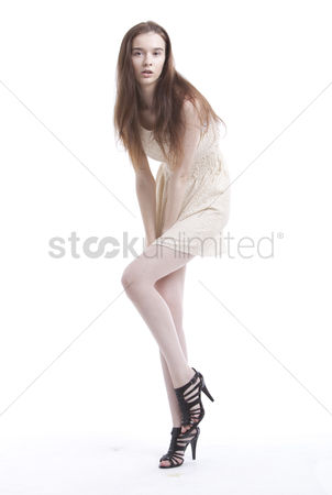 Fashion : Portrait of beautiful young woman in dress posing against white background