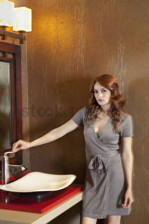 Interior : Portrait of beautiful young woman standing near sink in model home