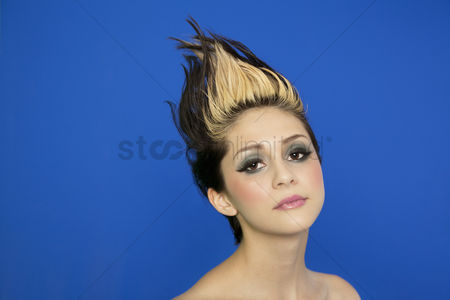 Head shot : Portrait of beautiful young woman with spiked hair posing over blue background