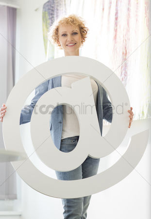 40 44 years : Portrait of confident businesswoman holding at sign in creative office