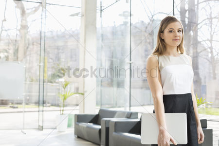 Occupation : Portrait of confident businesswoman holding laptop while standing at office lobby