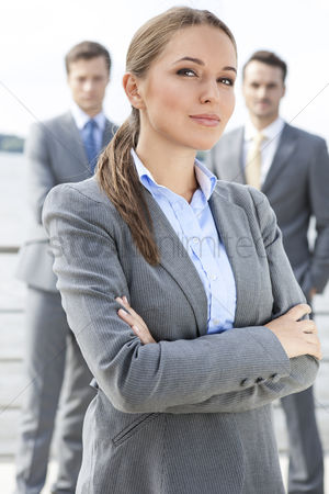 Leadership : Portrait of confident businesswoman standing arms crossed with coworkers in background on terrace