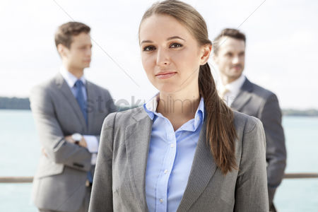 Leadership : Portrait of confident businesswoman standing with coworkers in background on terrace