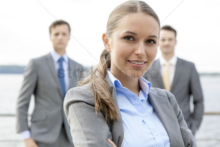 Leadership : Portrait of confident businesswoman standing with coworkers on terrace
