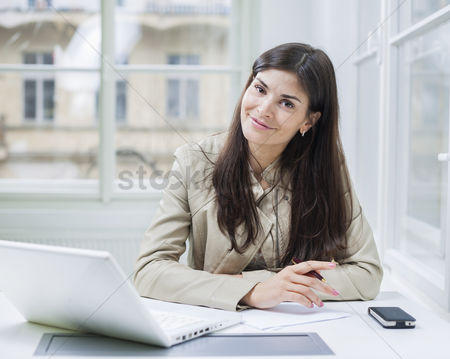 Office worker : Portrait of confident businesswoman with laptop sitting at office desk